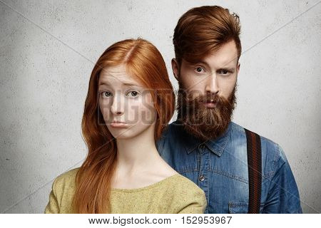 People And Relationships. Young Caucasian Couple With Unhappy Look Squabbling. Sad And Sulky Girl Wi