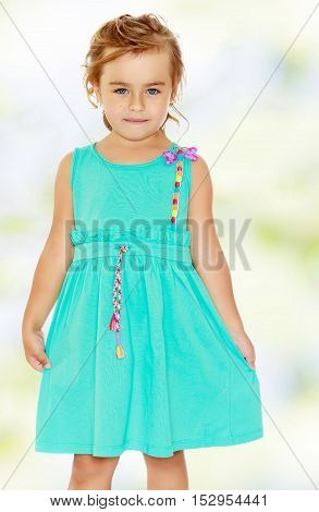 Stylish small, tanned girl in a blue dress with short sleeves. Close-up.Summer white green blurred background.