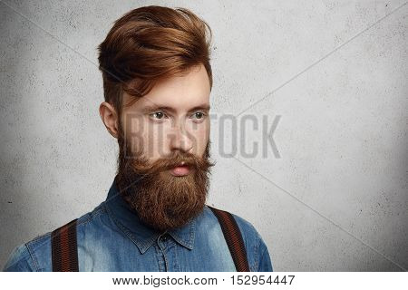 Fashionable Young Student With Stylish Haircut Spending Time Indoors, Standing Against Copy Space Wa