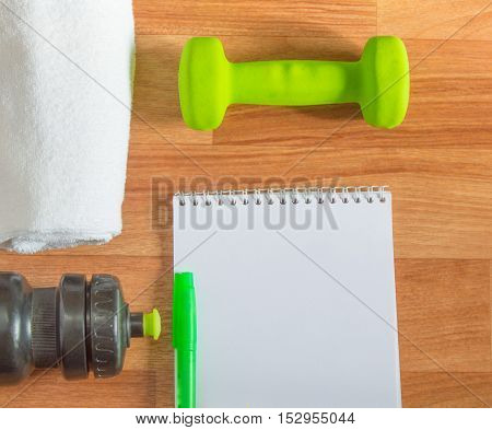 Plan workouts with dumbbells, towel, Water Bottle Notepad on wooden background