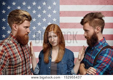 Doubtful Redhead Girl Choosing Between Two Young Handsome Men With Hipster Beards. Pretty Woman Tryi