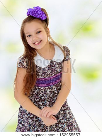 Happy long-haired little girl with a big purple bow on her head , and fancy dress. Close-up. Summer green and white background.