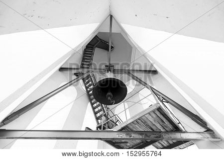 Belltower in church. Type of a bell from below. Black and white photo of a belltower. Belltower of the Russian church.