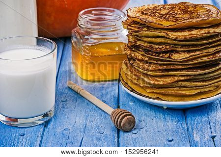 Stack of prepared pumpkin pancakes, glass and bottle of rmilk and jar of honey