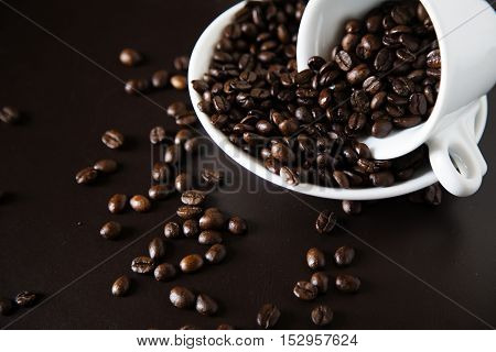 Brown coffee grains in a cup and on a saucer