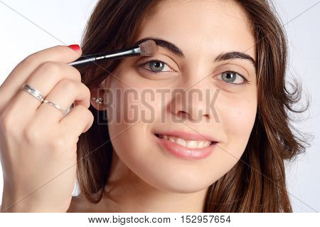 Young beautiful woman applying eyeshadow. Isolated white background.