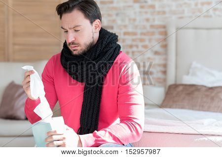 Having cold. Moody nice bearded man holding a box of paper tissues and taking one out of it while being ill