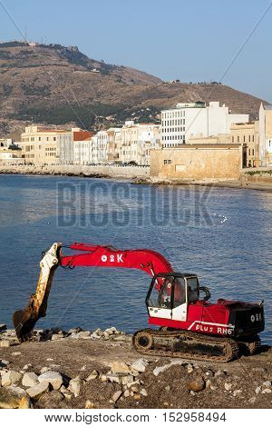 TRAPANI ITALY - AUGUST 10 2016: O&K Tracked Excavator RH6-22 on the waterfront in Trapani Sicily