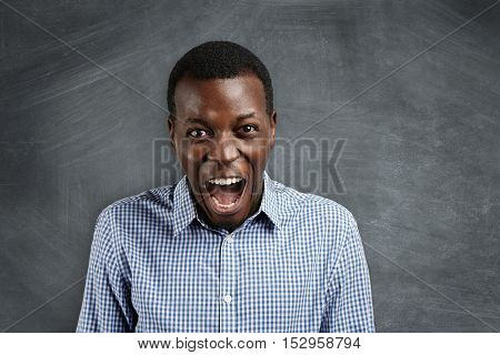 Negative Human Face Expressions And Emotions. Mad And Furious Young Dark-skinned Teacher Standing At