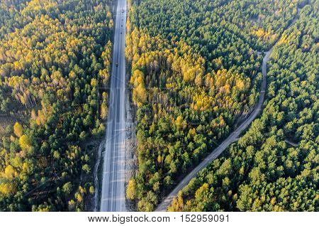 It's aerial view on the highway which go through autumn forest.