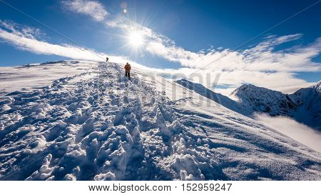 Tourists Enjoying High Mountains In Snow On A Sunny Day