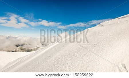 Mountain Tops In Winter Covered In Snow With Bright Sun And Blue Sky