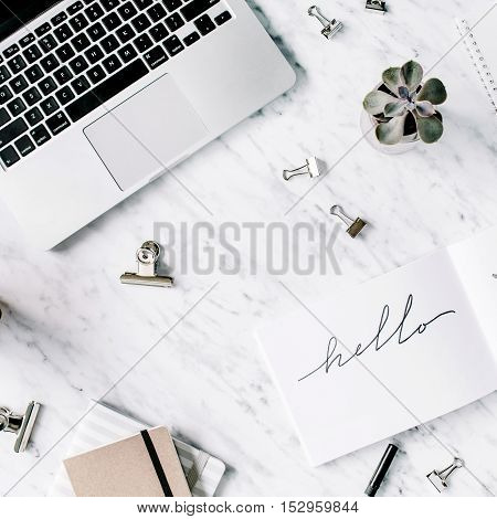 Word hello. Flat lay top view office table desk. Workspace with laptop diary succulent and clips on marble background.