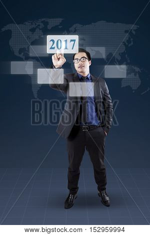 Full length of a young businessman pressing virtual numbers 2017 on the futuristic screen
