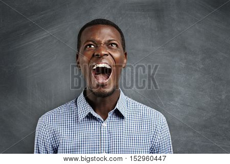 Negative Human Emotions. Portrait Of Angry And Irritated Young Dark-skinned Teacher Yelling During C