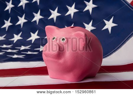 pink moneybox pig stands on the American flag