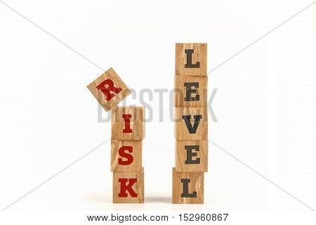 Risk Level word written on cube shape wooden surface isolated on white background.