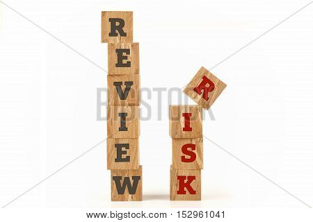 Review Risk word written on cube shape wooden surface isolated on white background.