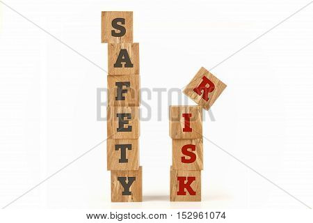 Safety and Risk word written on cube shape wooden surface isolated on white background.