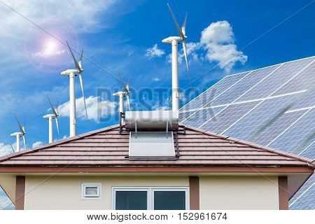 Solar panel for hot water system on roof and wind turbines blue sky background Energy saving and natural energy concept