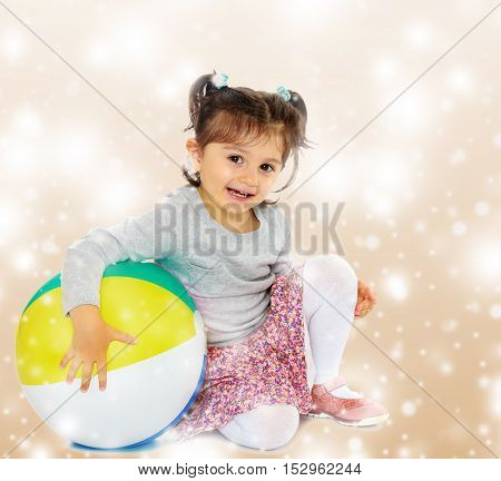 Cute little dark-haired girl with short pigtails on the head, hugging his big , inflatable, striped, vinyl ball.Brown festive, Christmas background with white snowflakes, circles.