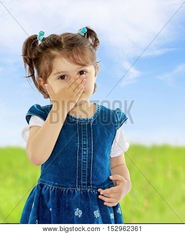 Unhealthy little girl with short pigtails on her head, closed his nose with his hand, the girl sneezes from allergies. Close-up.On the background of green grass and blue sky with clouds.