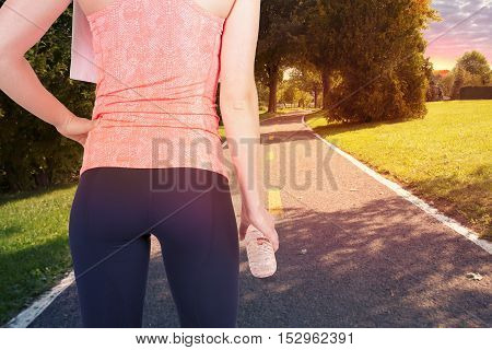 Running woman holding bottle of water ready to start.