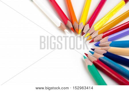 Colored pencils isolated on white background. Bright template with copyspace. Educational background.