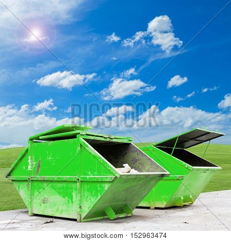 Industrial Waste Bin (dumpster) for municipal waste or industrial waste on green grass and blue sky backgroundwith ecology concept