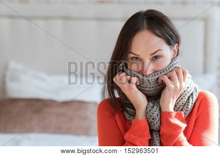 Keeping warmth. Good looking nice brunette woman standing in the room and looking at you while wearing a warm knitted scarf