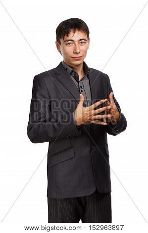 Young beautiful thoughtful man in dark grey lounge suit with short brunet hair standing with crossed fingers isolated on white background