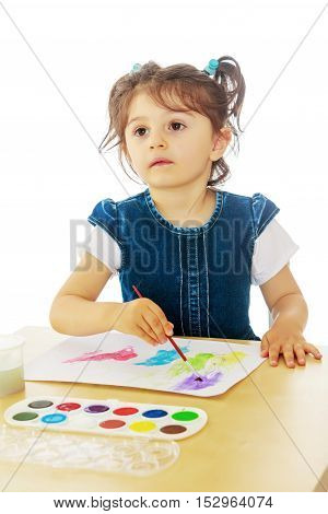 Cute little girl draws with watercolors on a sheet of white paper . Girl sitting at the table.Isolated on white background.