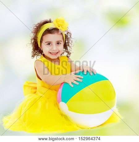 Joyful little girl in a yellow dress and bow on her head sitting on the floor. Girl hands hugging the ball.white-green blurred abstract background with snowflakes.