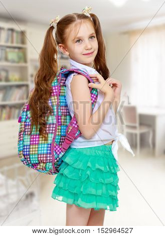 Cute little girl with long hair to the waist which wire braided white ribbons. In a white shirt without a pattern and green short skirt. The girl holds the shoulders schoolbag. Close-up - Isolated