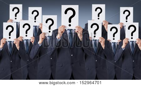 Group of humans hide their faces with question mark