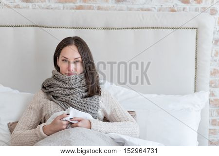 Bed rest. Beautiful positive young woman lying on the bed and smiling while having a bed rest