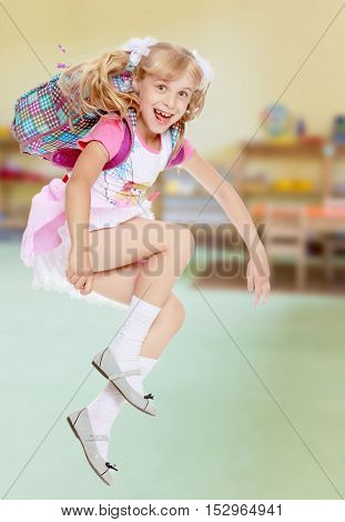 Cheerful little girl in a pink short skirt hurries to school.In the background children's room where there are shelves with toys.