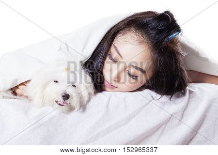 Image of pretty girl sleeping with her dog under blanket in the studio