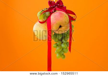 Pears and grapes with ribbon over orange background