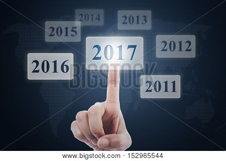 Picture of hand choosing and pressing a virtual button with numbers 2017 on the futuristic screen