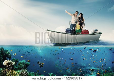 Portrait of happy family enjoying holiday while standing on the boat and carrying luggage at the sea