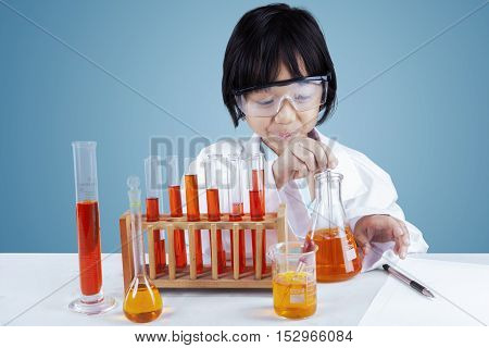 Photo of a little female scientist doing chemical tests with chemistry liquid on the table