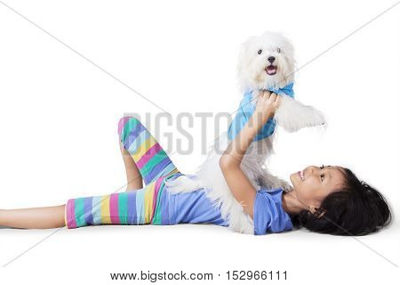 Image of a little girl playing with a maltese dog while lying in the studio