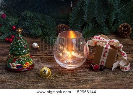 Christmas magic glowing light with evergreen tree and gift box on wooden background, low key