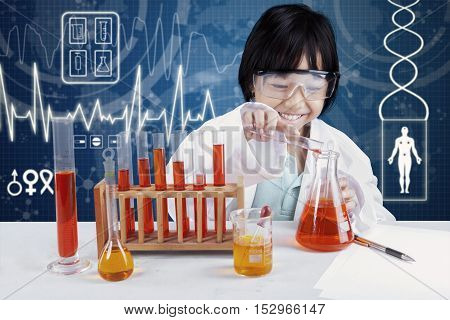 Photo of a little girl working as a scientist and making chemistry test in the laboratory