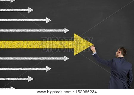 A business man is drawing Leadership concept with arrows on blackboard