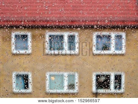 Raindrops on window glass with blurred building as background