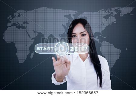Image of a pretty businesswoman pressing a virtual button with numbers 2017 and world map on the futuristic screen