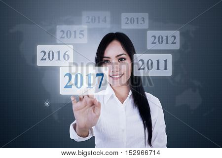 Portrait of beautiful businesswoman touching a virtual numbers 2017 on the futuristic screen