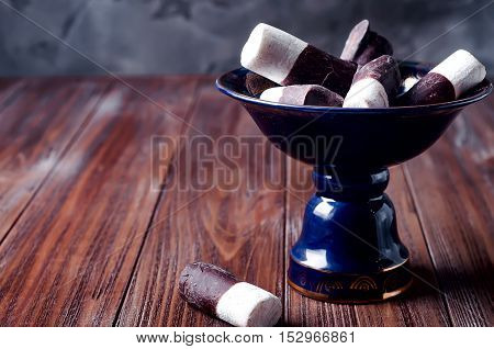 marshmallows and chocolate into a bowl on a dark background